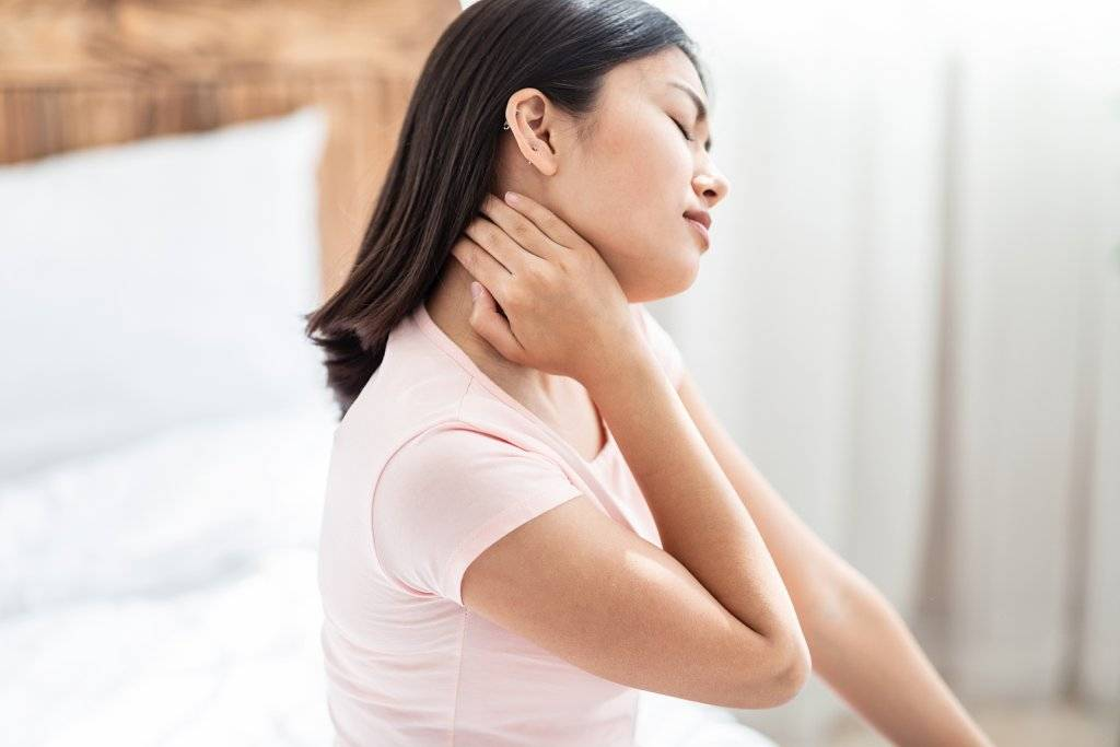 Asian Woman Having Arthritis Massaging Aching Neck Sitting In Bed At Home.