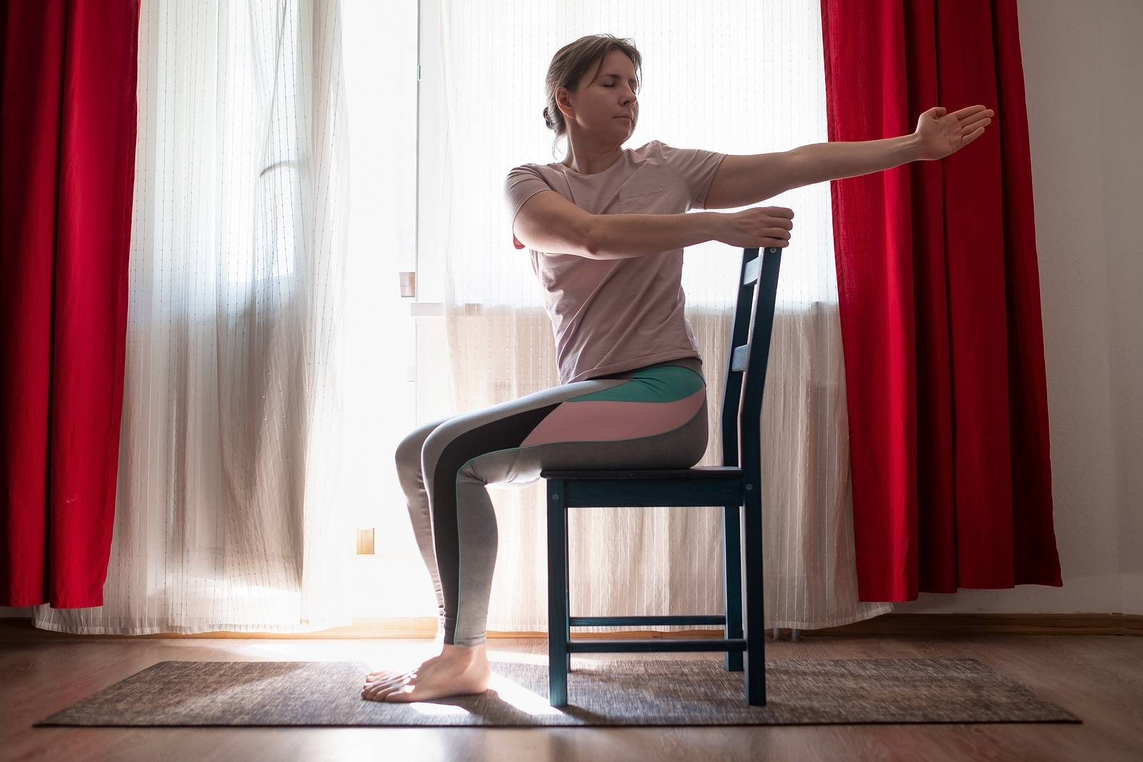 Woman working out doing yoga or pilates exercise using chair