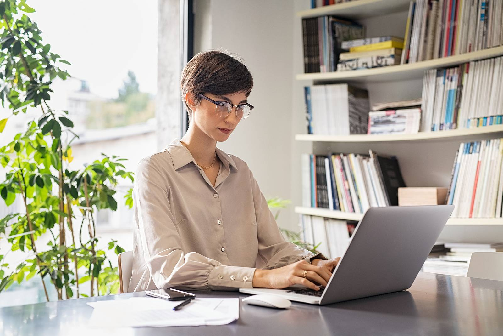 Young businesswoman sitting on her workplace in the office and working on laptop. Creative young woman using computer in meeting room. Business woman entrepreneur working from home in smart working.